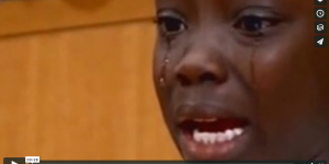 Still from video, young person wtih dark skin, looking past the camera in tears, with an expression of grief on their face