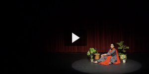 Person in an orange and purple robe sits on a stage near a plant, in front of a red curtain, reciting poetry.